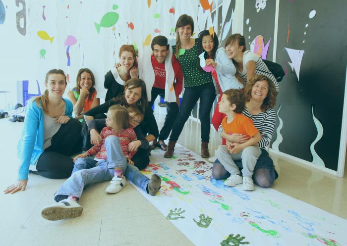 Grupo de personas adultas y niñas y niños sonriendo