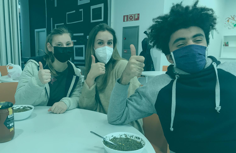 Tres jóvenes en el comedor sonríen a cámara.