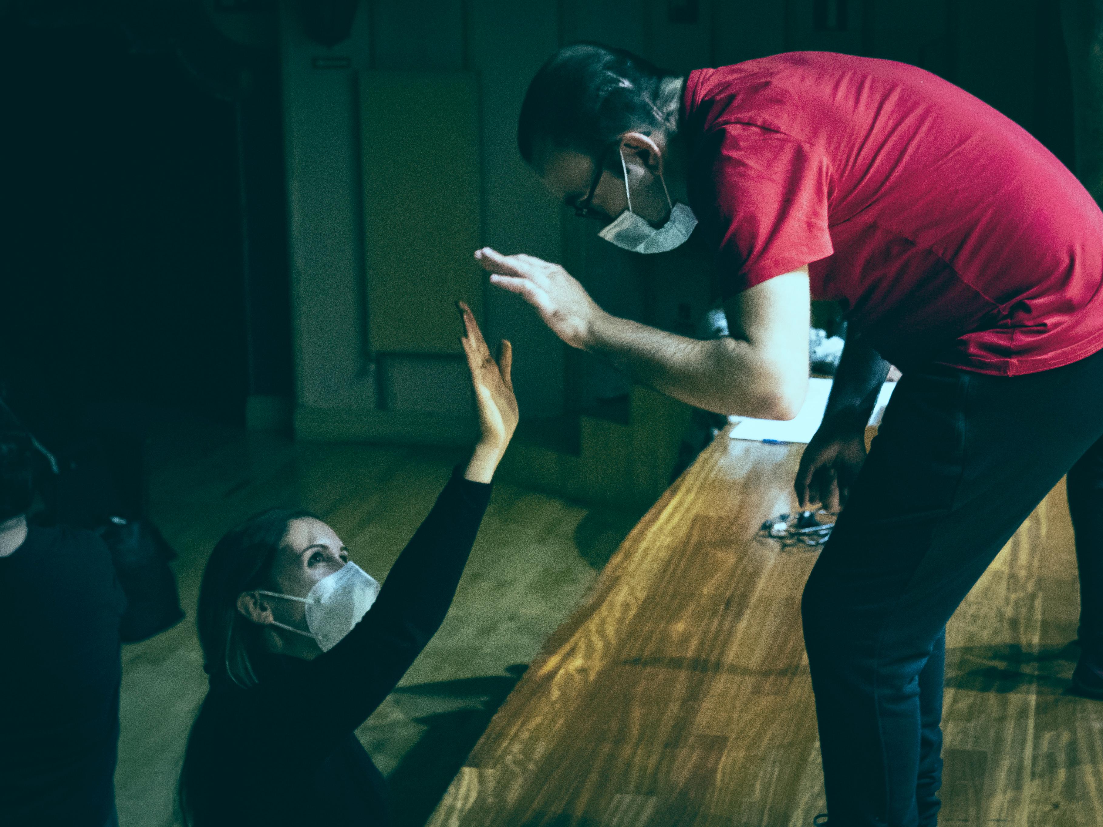 Mujer alcanzando con la mano a un hombre subido a un escenario