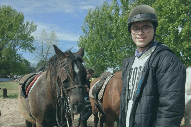 Chico al lado de dos caballos preparado para hacer hípica.