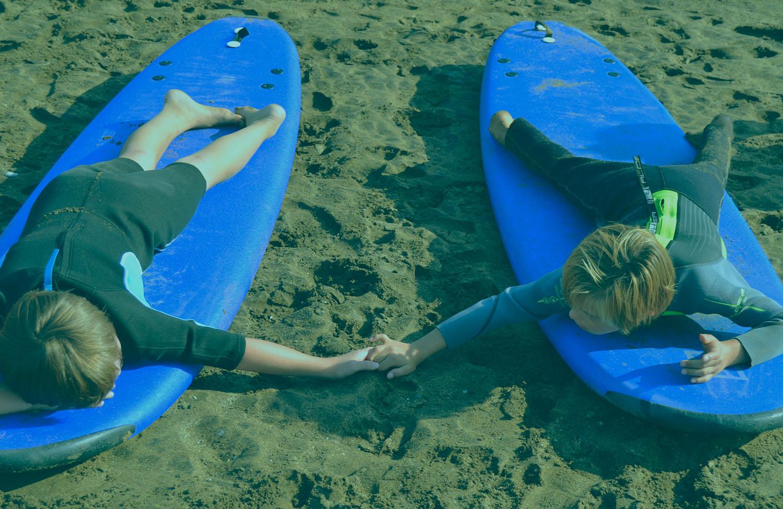 Dos niños encima de la tabla de surf.
