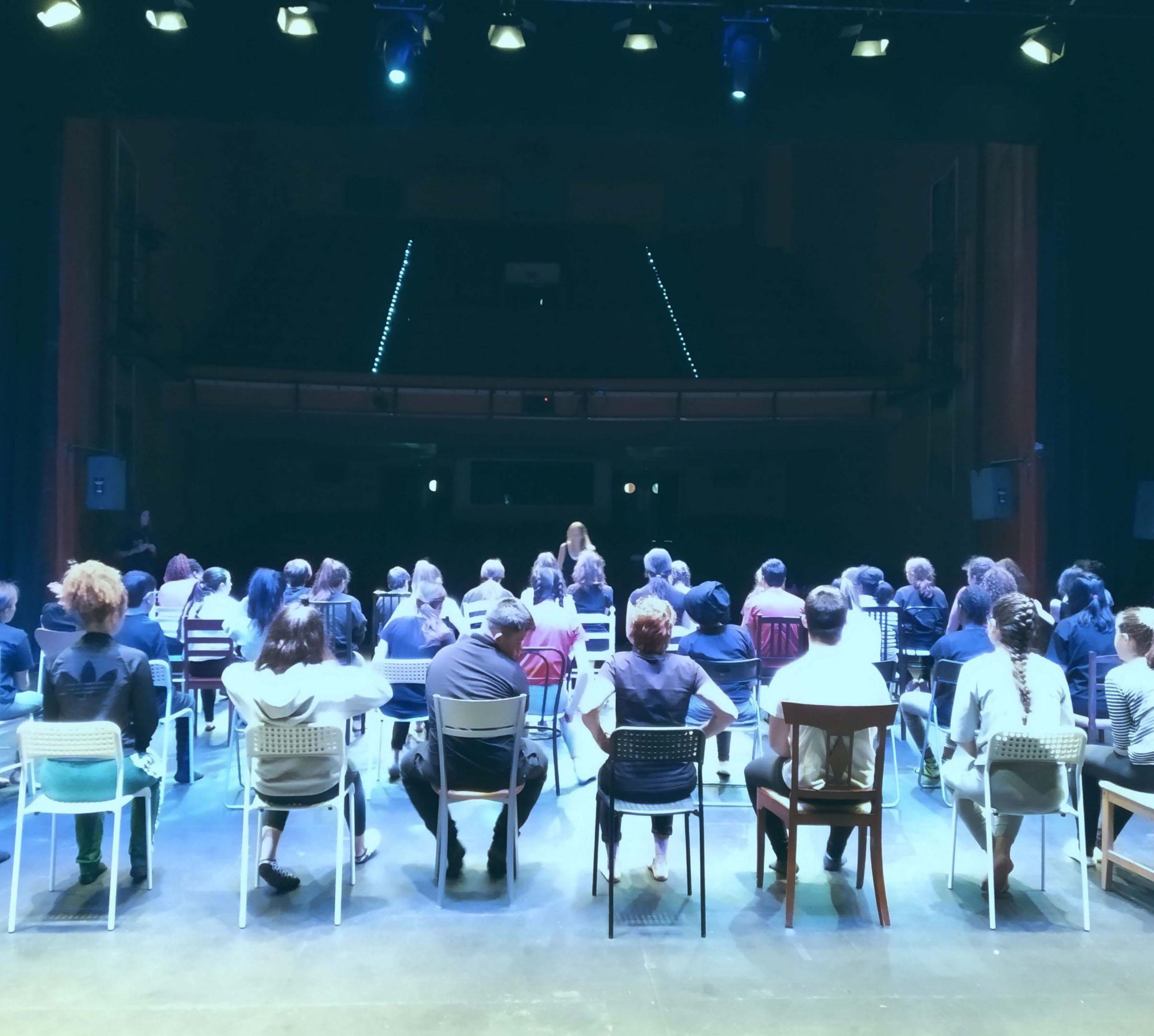 Función donde todas las artistas están sentadas como si fueran el público.