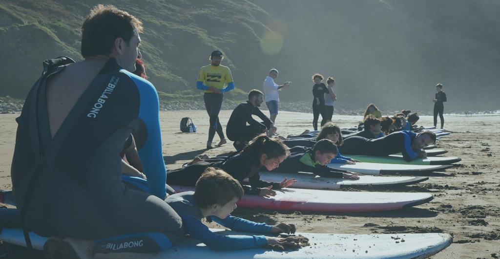 NIñas y niños aprenden a hacer surf tumbados en sus tablas encima de la arena